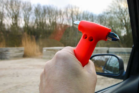 Safety hammer with  being used to break driver side window during car crash emergency