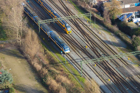 The Hague, the netherlands - February 2 2020: Dutch trains travelling on rail tracks shot from high angle drone style shot