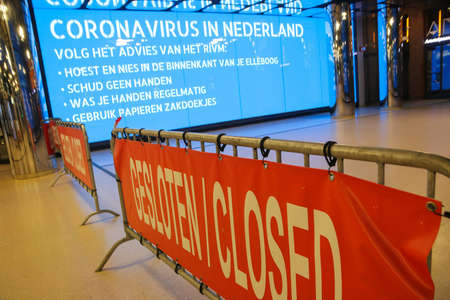 Amsterdam, the Netherlands - 18 March 2020: coronavirus warning alert on electronic billboard in a Dutch train station with barriers blocking entry