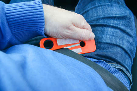seat belt cutter being used on seat belt during car crash emergency