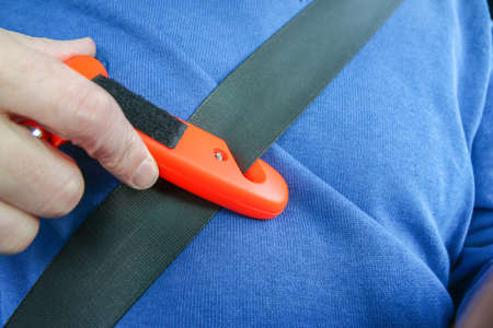 Safety hammer with seat belt cutter being used on seat belt during car crash emergency