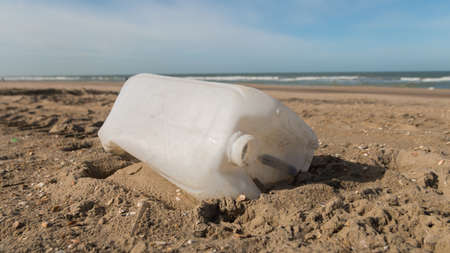 plastic liquid container discarded on a sandy beach with sea and blue sky in background