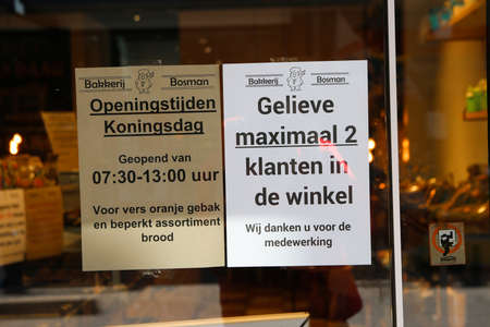Loosduinen, the hague, the netherlands - April 24 2020: warning sign in  shop window for 1.5 metre social distancing paying with pin and not hoarding