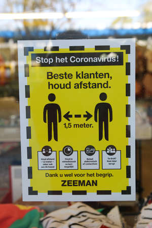 Loosduinen, the hague, the netherlands - April 24 2020: covid-19 warning sign in shop window for 1.5 metre social distancing and no more than 2 people inside