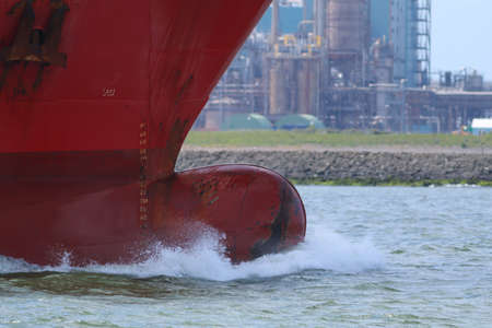 Bulbous bow of a ship with wave breaking before it as it passes industry of European port
