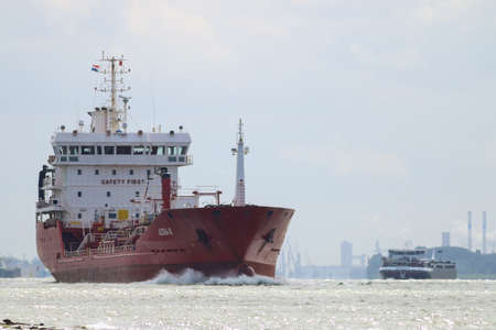 Hoek van Holland, Rotterdam, the Netherlands July 2 2020: red cargo freight ship leaving Rotterdam harbour in the Netherlands