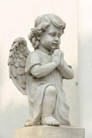 angel de la guarda: Linda estatua del ángel con alas en la oración, posan con vista lateral