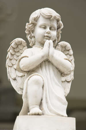 Cute winged Angel statue in praying pose in low angle view photo