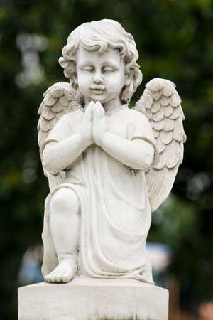 Cute winged Angel statue in praying pose photo