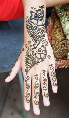 Muslim Lady hand being decorated with henna tattoo                photo