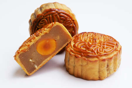 Three Tradditional Mooncakes with one cut up half to show egg yolk                    photo
