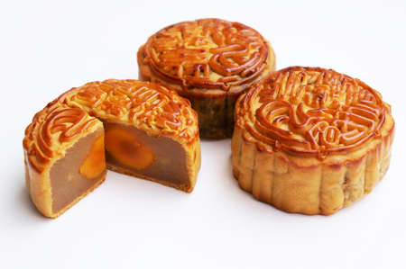 Three tradditional Mooncake with one cut up to show egg yolk                       Stock Photo