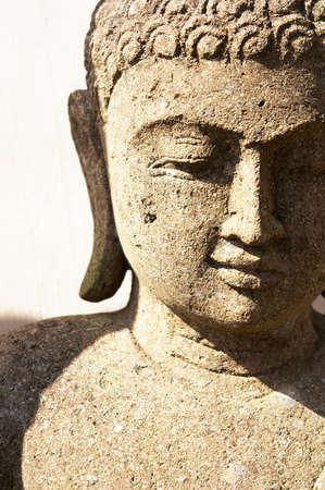 A stone Buddha Statue under bright sunlight.           Stock Photo