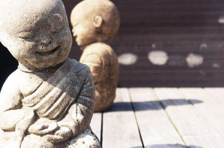 Two smiling stone monks sitting on wooden flooring                Stock Photo - 10883942