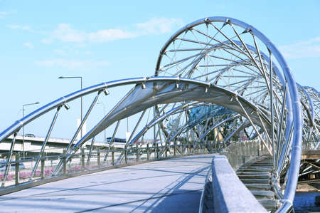 A metallic spiral structure bridge on top of a river.