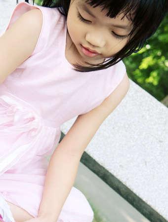 Rosa Kleid Mädchen sitzt auf Steinbank Befestigung Schuhe