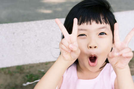 korean woman: Mischievous pink girl in a victory pose.   Stock Photo