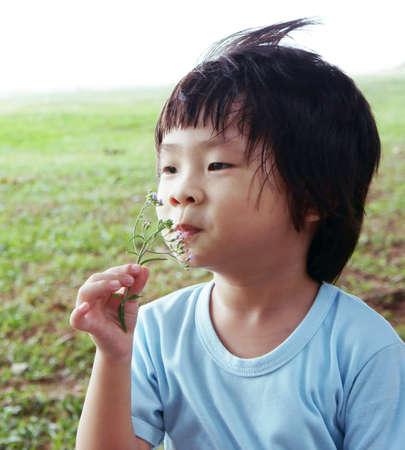 inhale: Romantic Boy smelling purple flower enjoying the breeze