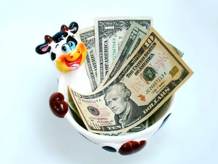 penny: A ceramic cow bowl holding USA dollars.           Stock Photo