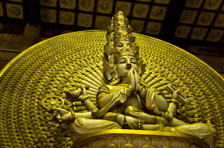A golden statue of Buddha with thousand hands