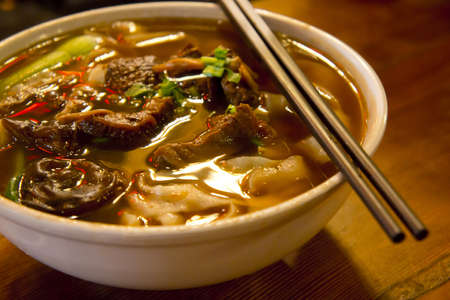 broth: Close up of a bowl of chinese style beef noodle soup.