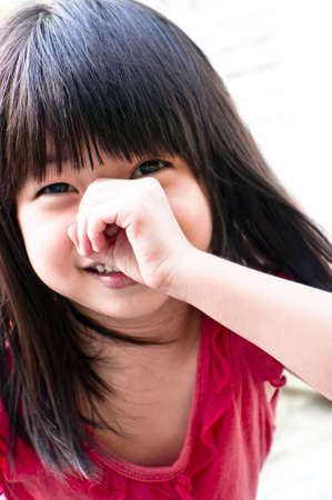 A playful asian girl covering her nose