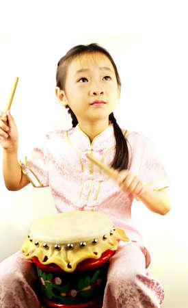 Asian Girl tragen traditionelle Tracht spielt Trommel