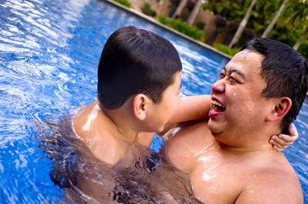 Asian Father and Son chatting happily in the pool  photo
