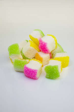 chewy: A pile of colorful soft chewy sugar coated sweet candies on white.