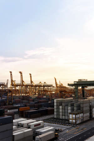 Vertical shot of a Harbor with lots of Cranes and cargo containers in a golden sunset view Editorial