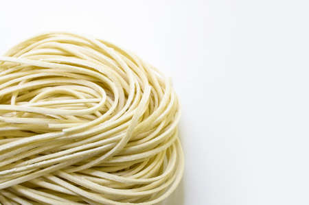 chinese noodle: Uncooked yellow noodles on white background   Stock Photo