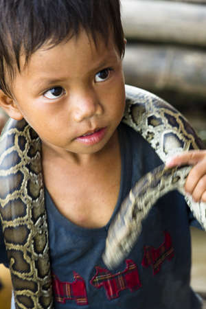 CAMBODIA – May 2012: Young Snake performer at Tonle Sap Lake in Cambodia in May 2012.  Living conditions in the area are difficult - Cambodia