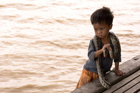 CAMBODIA – May 2012: Young boy playing with Snake at Tonle Sap Lake in Cambodia in May 2012.  Living conditions in the area are difficult - Cambodia