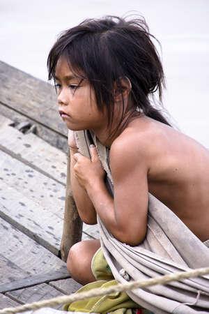 KAMBODSCHA - Mai 2012: Ein junges Mädchen Armut lustlos auf einer rauen hölzernen Boot segeln starrte in schwarzen Raum in Tonle Sap See, Kambodscha, Mai 2012. Die Lebensbedingungen in der Region sind schwierig - Kambodscha