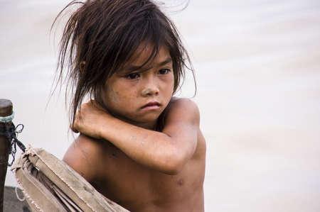 KAMBODSCHA - Mai 2012: Ein junges Mädchen Armut kratzt sich auf einer rauhen Holzboot Segeln im Tonle Sap See, Kambodscha, Mai 2012. Die Lebensbedingungen in der Region sind schwierig - Kambodscha Lizenzfreie Bilder - 14145569