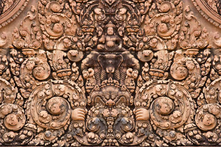 Red-colored intricate Hindu carvings at Banteay Srei temple of world-heritage site Angkor  Left Right seamless tile photo