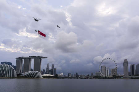 Three Helicopter fly through Singapore skyline carrying Singapore flag during Singapore National Day 2012