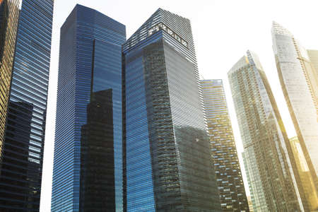 tall buildings: Close up of a cluster of modern glass buildings during sunset