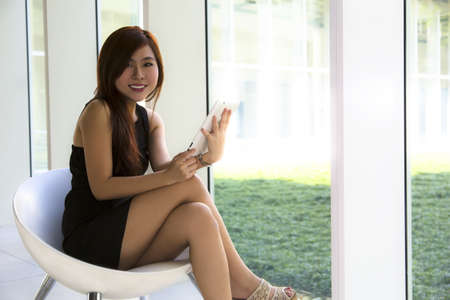 A young Asian executive in black seating holding on to a tablet   photo