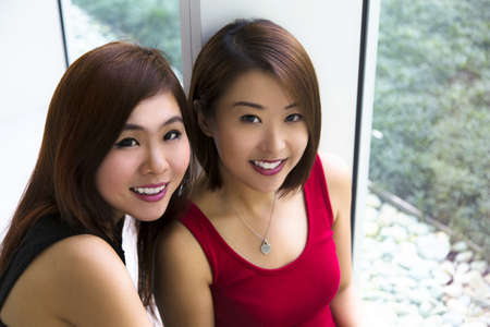 Close up of two charming Asian young ladies smiling  photo