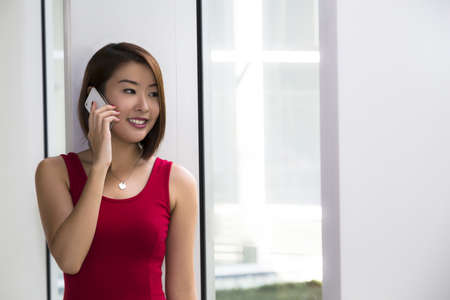 An Asian young lady making a phone call  photo