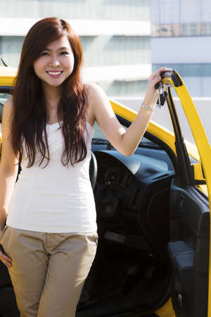 An Asian lady holding on to a set of car keys standing in front of a yellow car  photo