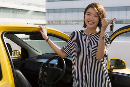 sell car: A young Asian lady holding car keys with her yellow car  Stock Photo