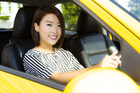 A charming Asian lady driving a yellow car   Stock Photo
