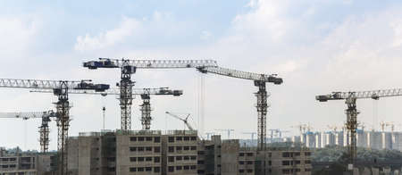 company building: Massive housing construction project with a lots of construction cranes and workers involve
