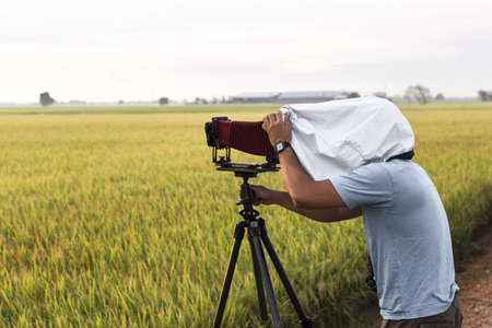 rarity: A photography hobbist with an old pavilion camera on a paddy field shooting sunrise