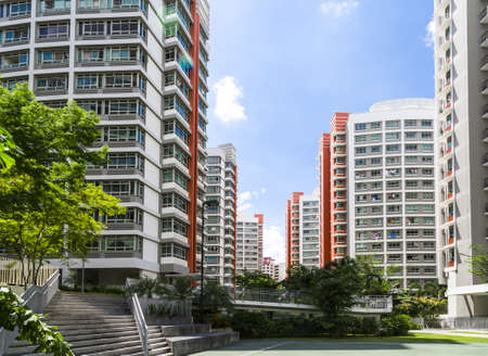 hdb: A flight of stairs leading to orange color residential estate with a basketball court- Singapore Editorial