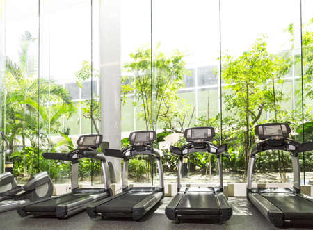 indoors: Four Treadmill in a gym with high ceiling in front of a big glass window
