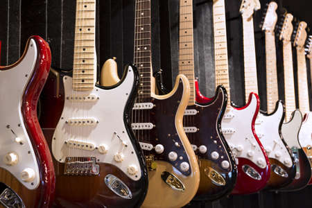 Many electric guitars hanging on wall in the music instrument shop