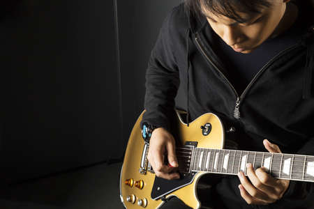 play popular: An Asian guitarist playing electric guitar with copy space on the left.